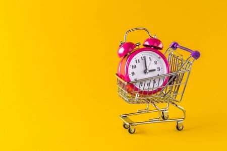 alarm clock and mini trolley cart with space copy on Yellow background. red alarm clock in beautiful shopping cart. minimal concept with copy space.