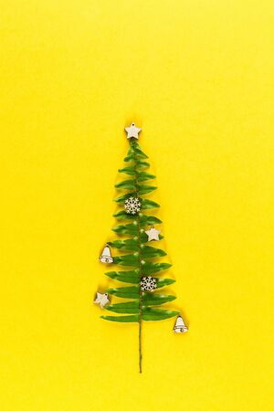 Christmas tree made of fern leaves and branches on yellow pastel trendy background. Merry Christmas and Happy New Year greeting card. Minimal winter background. Flat lay. Copy space for the text