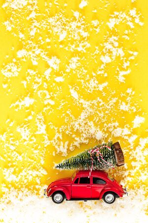Red toy car with a christmas tree on the roof. Old antique toy carrying a Christmas tree. New Year minimal concept with copy space. Template mockup for greeting card your text design