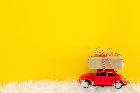 Red toy car with a christmas tree on the roof. Old antique toy carrying a Christmas gift box. New Year minimal concept with copy space. Template mockup for greeting card your text design