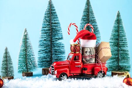 Izhevsk, Russia, November 03, 2019. Retro toy truck carrying a Christmas money gift in snowy landscape. Merry Christmas and Happy New Year greeting card Stock Photo