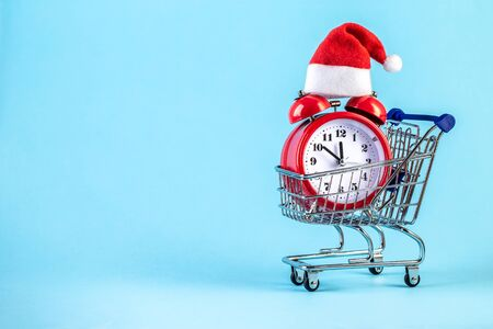 Christmas alarm clock in a supermarket trolley on a blue background. Alarm clock with Santa Claus hat. Merry Christmas and Happy New Year concept. Template mockup for greeting card your text design