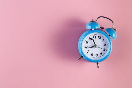 Blue vintage alarm clock on light pink color background. Alarm clock with place for text. Time management concept, business planning Reklamní fotografie