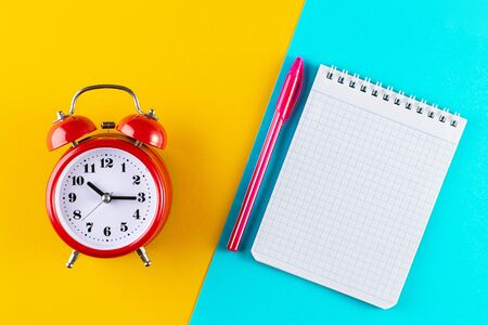 Retro alarm clock next to a pen and notebook on a blue and yellow background. Studying at school and university. Time management concept, business planning. Top view, Flat lay Reklamní fotografie