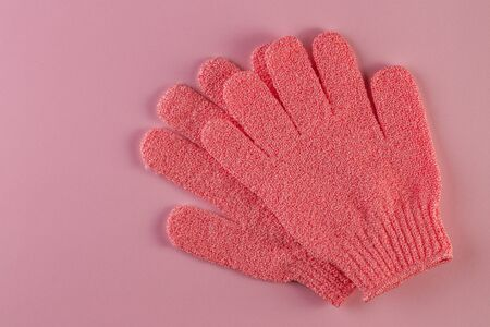 A pair of pink massage gloves for shower on pink background. Gloves for use in the shower for massage and scrub. Beauty background with cosmetic products. Beauty, health and spa concept