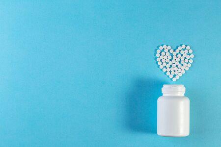 Pilules blanches en forme de coeur avec bouteille sur fond bleu. Banque d'images