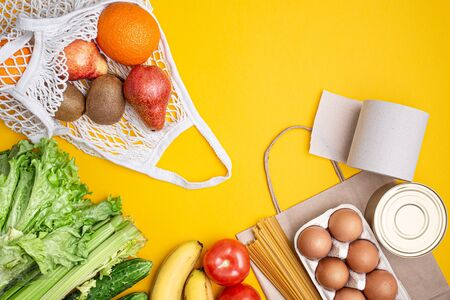 Paper bag with food, canned food, tomatoes, cucumbers, bananas on a yellow background. Donation, coronavirus quarantine. Food supplies for quarantine. Food delivery. Copyspace.