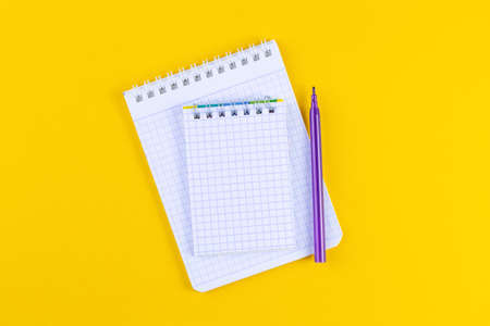 Open notebook on bright yellow paper background with pen.