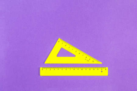 School drawing tools. Yellow triangle and ruler on a purple background