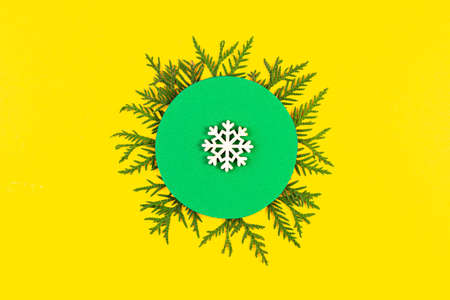 Christmas banner with coniferous tree branches and snowflake on yellow paper background. Round frame of Christmas tree branches and decorations with space for text. Top view. New year concept