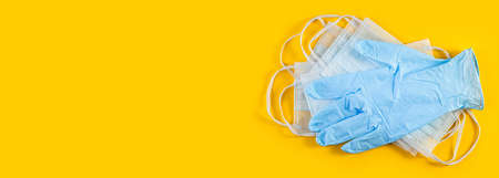 Long wide banner. Pair of latex medical gloves and surgical ear-loop mask on yellow background. Hygiene protection Coronavirus Covid 19. hygiene items consisting of latex gloves and mask 写真素材