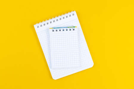Open notebook on bright yellow paper background. School accessory with copy space on color background. The concept of studying or planning. Flat lay.