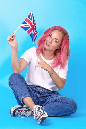 Young girl student points to the flag of Great Britain, urging her to learn English on blue background. Learn English. study abroad, international language courses.