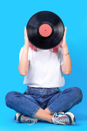 Woman dj portrait with vinyl record against blue background. Retro picture of woman with vinyl record Imagens