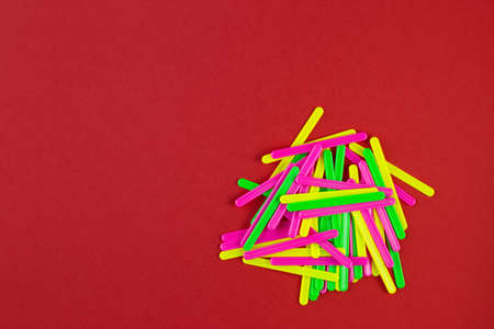 Counting sticks of different colors for classes with children on red paper background with copy space. school stationery. Preparing for school with copy space