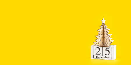 Minimalistic Christmas tree on yellow pastel trendy background. Winter holiday concept. Long wide banner.