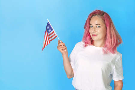 Young girl student holds american small flag and smiles on blue background