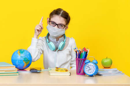 The schoolgirl at her Desk in a medical mask on yellow background Imagens