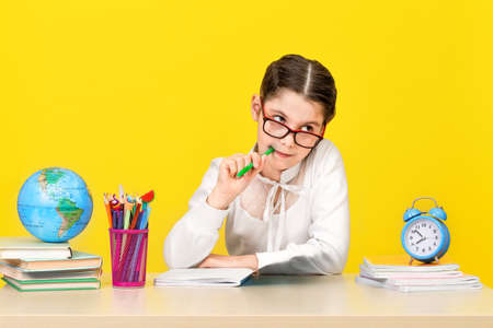The schoolgirl sits at the desk and thinks about the decision of the task on yellow background.