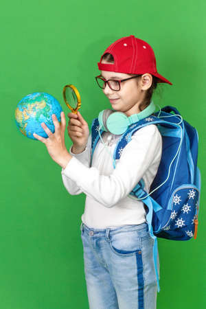 Portrait of a little schoolgirl with a backpack holding a globe in her hands 写真素材