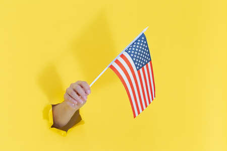 Hand from a hole in yellow paper holds an American flag with blue stars. 写真素材