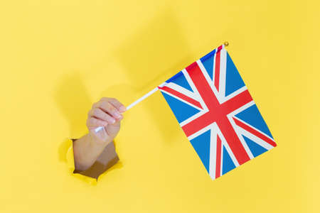 Hand holding English flag from yellow torn paper. United Kingdom flag