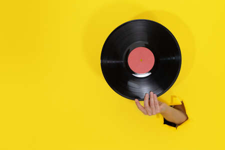 Female hand holding Vinyl Record through torn hole in yellow paper wall 写真素材