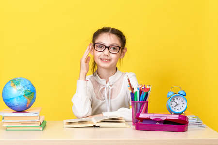 The schoolgirl sits at the desk and raises her hand for an answer. Back to school. The new school year.