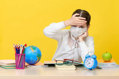The schoolgirl at her Desk in a medical mask on yellow background 写真素材