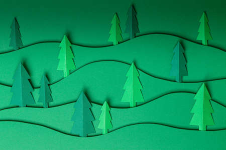 3D pop out Christmas trees paper artwork in green background. paper cutting design card. 写真素材