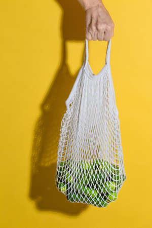 Male hand holding a white mesh bag with cucumbers on yellow background 写真素材