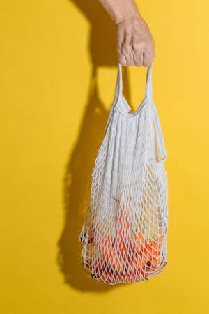 Male hand holding a white mesh bag with carrots on yellow background 写真素材