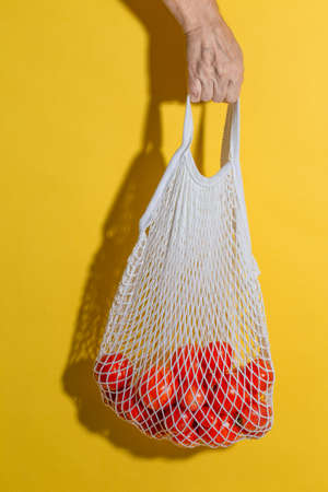 Male hand holding a white mesh bag with tomatoes on yellow background 写真素材 - 157386369