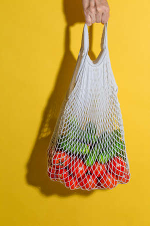 Male hand holding a white mesh bag with vegetables on yellow background 写真素材