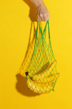 Male hand holding a green mesh bag with bananas on yellow background 写真素材