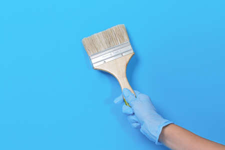 Brush for paint in hand on a blue background.