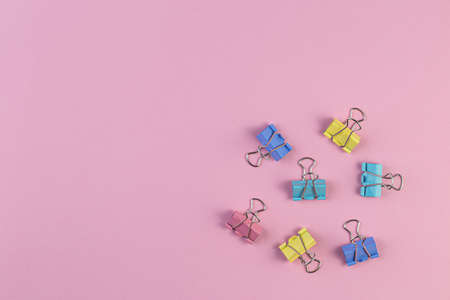 Colored iron paper clips on a pink background. Space for text.