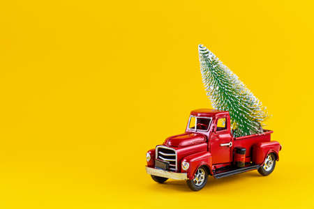 Red retro toy truck with Christmas tree on truck body on yellow background.