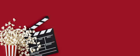 Watching movie with popcorn and clapperboard on red background. Movie goers accessories, cinematography concept. Long wide banner with copy space Archivio Fotografico