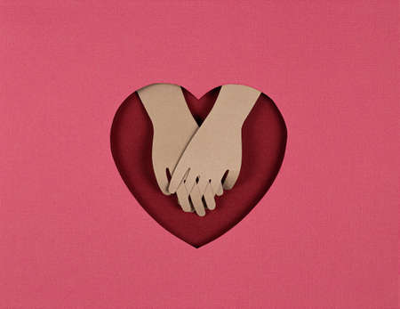 Valentines Day card. Creative paper cut background with Origami Heart and look of the lovers hands. Holding hands on red heart. Paper art on valentine day. paper cut and craft style 写真素材