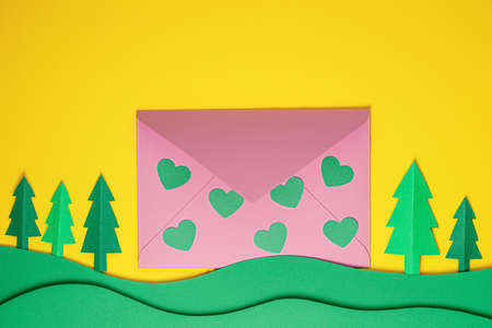 Festive card. Paper green hearts and pink envelope on yellow background. Creative paper cut background with paper envelope. Paper art on valentine day, birthday, wedding. Flat lay, copy space