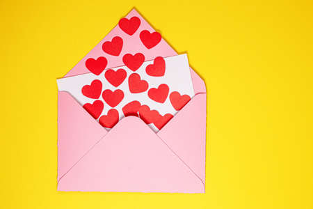 Valentines Day card. Paper red hearts fly out of pink paper envelope on yellow background . Paper art on valentine day. paper cut and craft style. Space for text. concept of Valentines Day