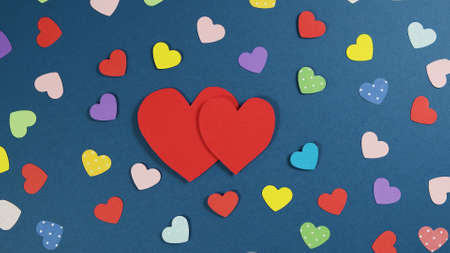 Holiday Abstract Valentine Background with multicolored paper Hearts. Cutted paper heart on blue background, paper cut out art style. Valentine Day Paper Crafts