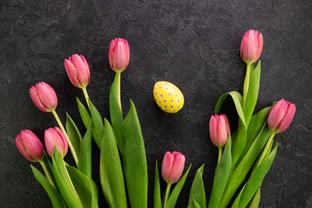 Easter egg and pink tulips on a dark concrete background. Hello spring and easter concept. 写真素材