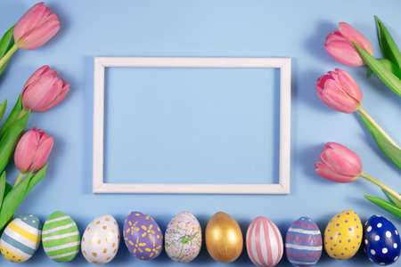 Tulips flowers and Easter eggs with wooden frame on blue background. Card for Happy Easter