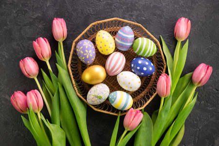 Basket with easter eggs and pink tulips on a dark concrete background. Hello spring and easter concept.