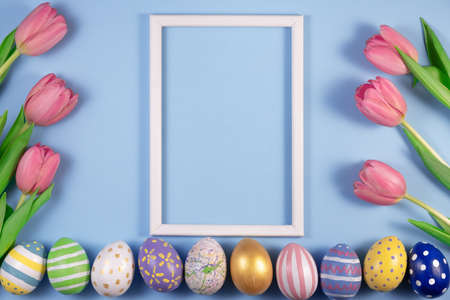 Tulips flowers and Easter eggs with wooden frame on blue background. Card for Happy Easter.