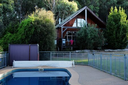 An outdoor pool in front of a wooden country cottage surrounded by trees and bushes