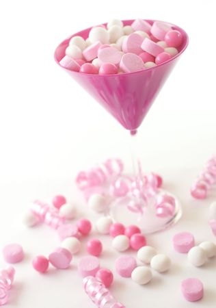 Pink and white candies in a pink martini glass with decorative ribbons. Stock Photo