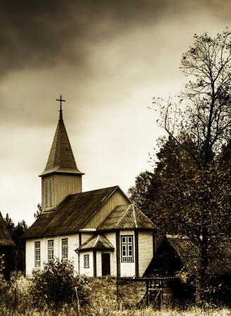 country church: Wooden catholic church under heavy skies Stock Photo